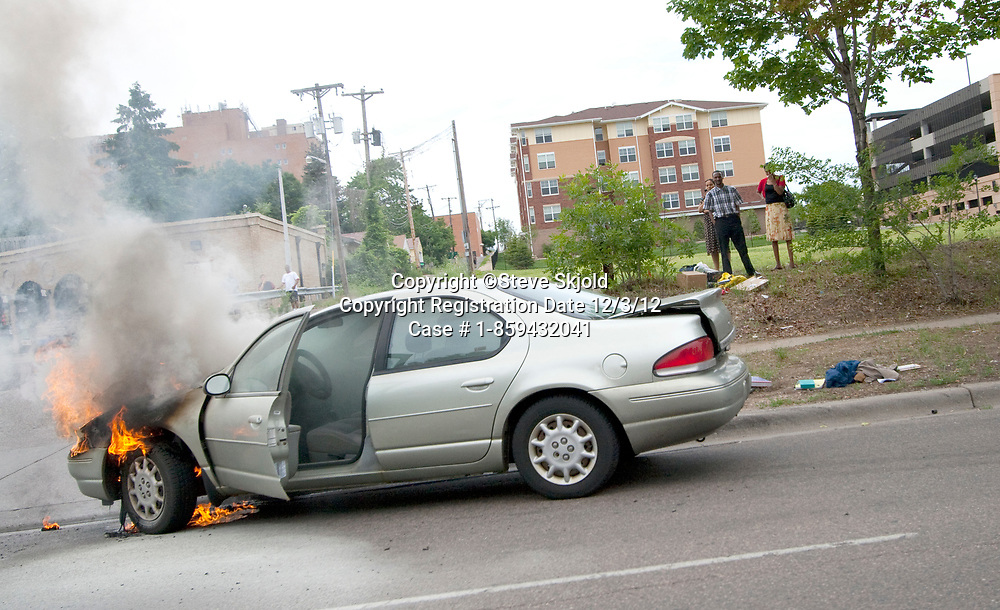 Car on fire as passengers watch with their rescued belongings. St Paul Minnesota MN USA