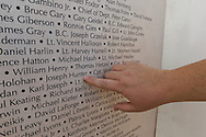 """East Meadow, New York, U.S. 11th September 2013. ROSEMARY HUNTER, of Wantagh, points to name of her brother-in-law, Joseph G Hunter, during her visit to the Global War on Terror """"Wall of Remembrance"""" a traveling memorial on display in New York for the first time, at Eisenhower Park on the 12th Anniversary of the terrorist attacks of 9/11. Joseph Hunter was a firefighter in Squad 288 in Maspeth Queens who died September 2001. The unique 94 feet long by 6 feet high wall has, on one side, almost 11,000 names of those lost on September 11, 2001, along with heroes and veterans who lost their lives defending freedom of Americans over past 30 years. On the wall's other side is a timeline, with photos, covering 1983 to present day."""
