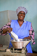 Joyce Marwa weighing flour on some scales.<br /> <br /> Joyce set up and now runs a bakery that bakes bread and cakes. She also processes nutritious flour (a mix of 5 grains)<br /> <br /> She attended MKUBWA enterprise training run by the Tanzania Gatsby Trust in partnership with The Cherie Blair Foundation for Women.