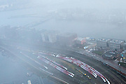 Nederland, Noord-Holland, Amsterdam, 16-01-2014;<br /> Oostelijk Havengebied in de mist met het rangeerterrein waar de buiten dienst gestelde Fyra-treinen staan opgeslagen. Nieuwbouw langs IJ-Haven en in de achtergrond Java-eiland met woonwijk.<br /> Shunting-yard in foggy weather with the international Fyra train units parked along the Piet Heinkade in the Oostelijk Havengebied. <br /> <br /> luchtfoto (toeslag op standard tarieven);<br /> aerial photo (additional fee required);<br /> copyright foto/photo Siebe Swart