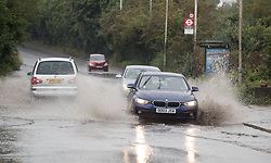Cars goes through a large puddle near Colnbrook, Berkshire as a yellow weather warning for rain has been issued for parts of the UK.