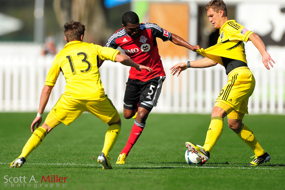 Toronto FC defender Ashtone Morgan (5) grabs the jersey of Columbus Crew midfielder Konrad Warzycha (19)  as they fight for a ball during the Disney Pro Soccer Classic on Feb 9, 2013  in Lake Beuna Vista, Florida. ..©2013 Scott A. Miller