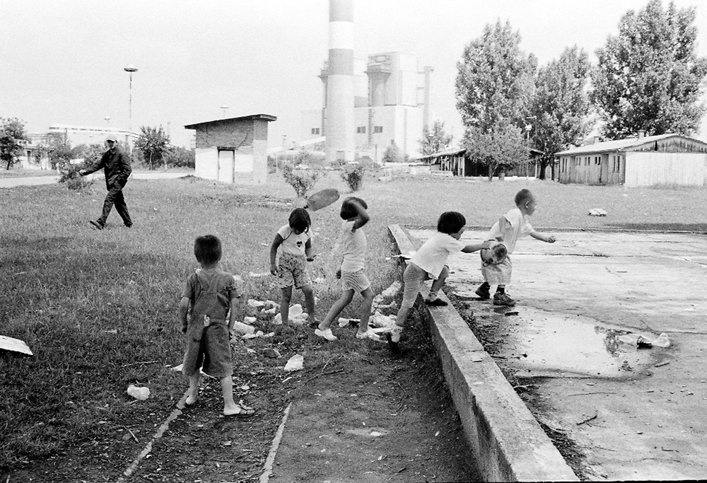 Children playing in front of an industrial plant...During the summer1999, over 245,000 Serbs and Roms fled to Serbia and Montenegro from or within Kosovo in fear of reprisals from the majority Albanian population, after NATO air strikes had forced the withdrawal of Yugoslav. In 2003, less than 2% of them had returned and a large number of these internally displaced persons (IDPs) were still living in camps in very difficult conditions..In addition, around 5,000 IDPs, mainly of Roma ethnicity, are living in unrecognized collective centres, makeshift huts, corrugated metal containers and other substandard shelters. .This work  was meant to look at how the life of children and young adults is affected by the fact that they are IDPs. I asked myself more specifically what would be different for these children/young adults from the 'normal' people of their age as far as education, health, social life, family, 'love' life and leisure are concerned. ..Enfants jouant près d'une usine...Pendant l'été 1999, plus de 245 000 serbes et roms ont fuit le Kosovo pour chercher refuge en Serbie ou au Montenegro, par peur de représailles de la part de la majorité de la population albanaise après que les forces de l'OTAN aient forcé l'armée yougoslave à se retirer. En 2003, moins de 2% d'entre eux étaient rentrés chez eux et le plus grand nombre de ces 'déplacés' (IDPs) vivaient encore dans des centres d'accueil dans des conditions très difficiles..Environ 5 000 IDPs, la plupart romas, vivent dans des centres non reconnus faits de containers ou d'abris de fortune. .Ce travail s'est focalisé sur les jeunes IDPs, sur les conséquences de leur état de 'déplacés' sur leur vie et plus particulièrement dans les sphères concernant l'éducation, la santé,  la vie sociale, la vie de famille, la vie amoureuse et les loisirs..