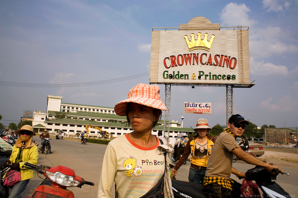 Cazino sign and moto-taxi drivers. In the no-mans-land  between the border of Thailand and Cambodia near the Thai border town Aranyaprathet, there is a cazino town where mainly Thai customers go for a day or two to visit any of the 8 fancy cazinos there. At the same time, every morning Cambodian people cross the border on foot to go to their jobs in Thailand and the come back in the evening. Goods are also transported on wooden handheld carriages from one side to the other, passing through the Khmer gate that lays in the middle.
