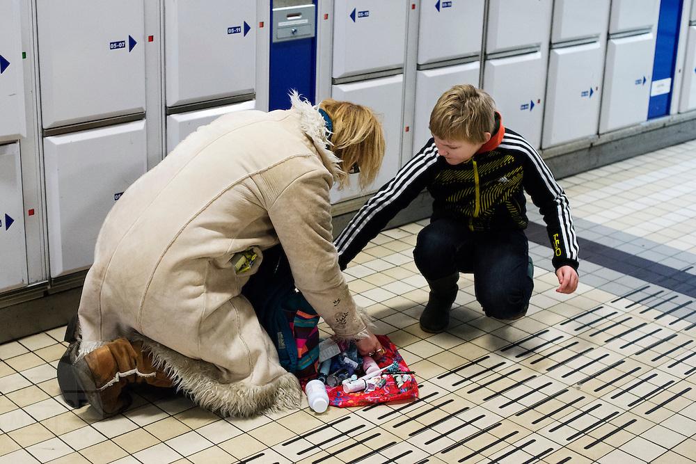 Een jongen helpt een vrouw met het weer inpakken van de handtas.<br /> <br /> A boy is helping an woman to pack her handbag.
