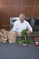 Mid- adult chef washing leaf vegetables in sink