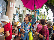 15 OCTOBER 2014 - BANGKOK, THAILAND: A tour guide carries an umbrella so tourists can follow him through the streets of Bangkok. The number of tourists arriving in Thailand in July fell 10.9 per cent from a year earlier, according to data from the Department of Tourism. The drop in arrivals is being blamed on continued uncertainty about Thailand's political situation. The tourist sector accounts for about 10 per cent of the Thai economy and suffered its biggest drop in visitors in June - the first full month after the army took power on May 22. Arrivals for the year to date are down 10.7% over the same period last year.   PHOTO BY JACK KURTZ