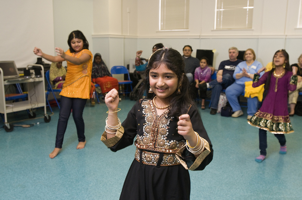 Dance students Arika Diwedi, 10, left, Kavya Nair, 10 (not shown), Preeti Tanwani, 8, center, and Shloka Nair, 9, demonstrate Nachale: The Bollywood Dance Workout, during the English Conversation Club: Dance and Dialogue event Saturday April 9, 2011 at the Iroquois Branch of the Louisville Free Public Library in Louisville, Ky. Henna and Bindi followed the Bollywood dance lesson, and then volunteers were paired with English language learners to work on conversation skills. (Photo by Brian Bohannon)