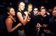 A man with bleached, styled hair poses with drunk friends at a nightclub, London, U.K, 1990s.