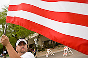 10 APRIL 2006 - PHOENIX, AZ: A man carries an American flag through Phoenix, AZ. More than 200,000 people participated in a march for immigrants's rights in Phoenix Monday. The march was a part of a national day of action on behalf of undocumented immigrants. There were more than 100 such demonstrations across the US Monday. Protestors were encouraged to wear white, to symbolize peace, and wave American flags, to demonstrate their patriotism to the US.  Photo by Jack Kurtz