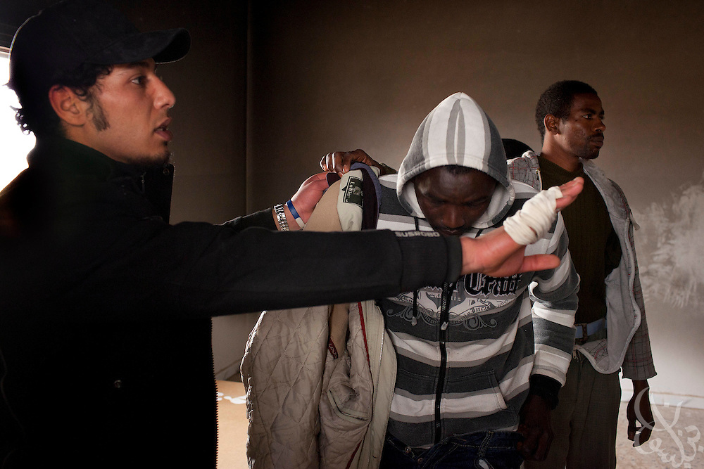Libyan opposition rebels question a group of African immigrants they suspect might be pro-Qaddafi mercanaries at a checkpoint March 03, 2011 in Ajdabiya, Libya.  The area around Ajdabiya and nearby Brega is tense following an attack by militiamen and airstrikes in the area. The African men were questioned, searched and later released..Slug: Libya.Credit: Scott Nelson for the New York Times