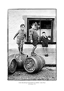 Young boys playing on beer barrels in Castlebar, County Mayo.<br />