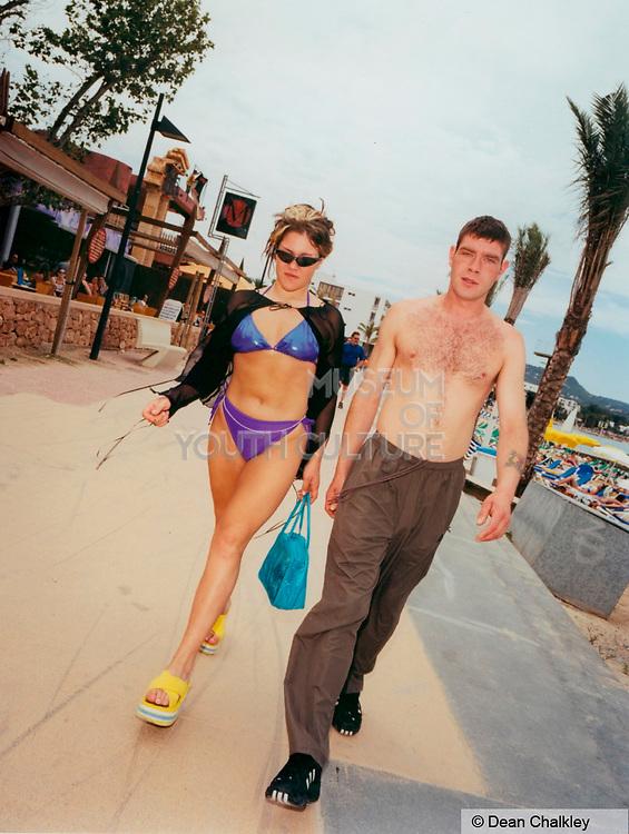 Couple walking down the street woman wearing a purple bikini Ibiza 2001