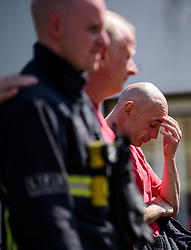 © Licensed to London News Pictures. 19/06/2017. London, UK. Firefighters who attended the scene of the fire observe minutes silence held near the scene of the Grenfell tower block fire. The blaze engulfed the 27-storey building killing dozens - with 34 people still in hospital, many of whom are in critical condition. Photo credit: Ben Cawthra/LNP