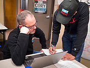 19 DECEMBER 2019 - URBANDALE, IOWA: JEREMY JONES, a campaign volunteer, learns about the phone bank from DEEPAK JONNALAGEDDA, right, a member of Sen Booker's campaign staff at Sen. Cory Booker's campaign headquarters in Urbandale, a suburb of Des Moines. Sen. Booker, who did not qualify for the December 19 debate in Los Angeles, campaigned in the Des Moines area Thursday and visited the phone bank at his Iowa campaign headquarters.               PHOTO BY JACK KURTZ