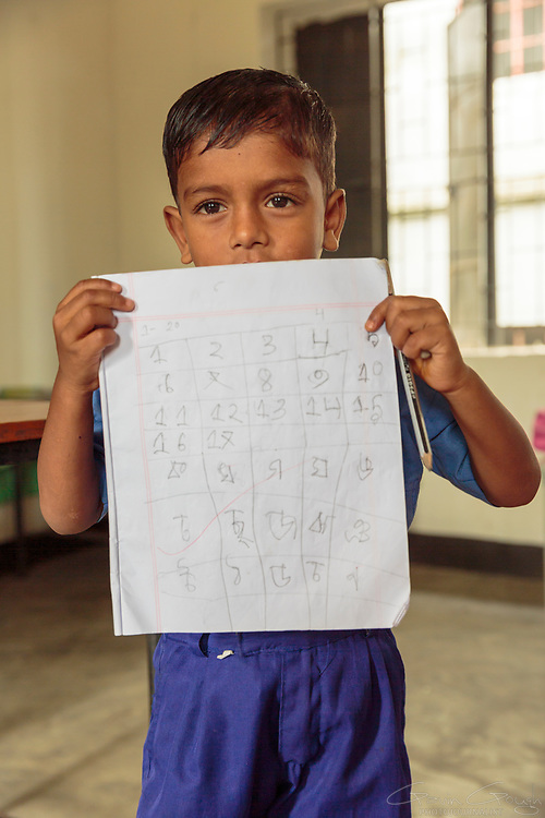 A boy in a primary school class holds up his class work