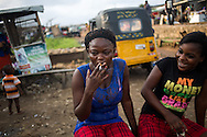 """Friends share a cigarette in front of a brothel at a small vendor stall selling herbal tonics along the tracks in the Badia neighborhood of Lagos, Nigeria, August 30, 2013.  Among the tonics sold by this vendor is one for """"taking out the pregnancy."""""""