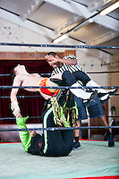 Man lifting rival while wrestling in ring