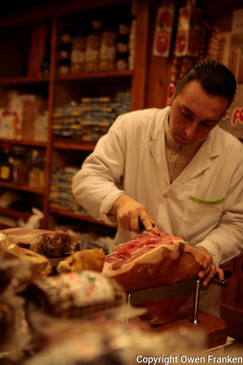 ROME - man slicing cured hams