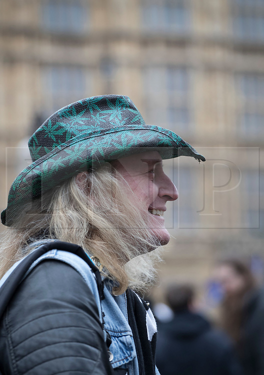 © Licensed to London News Pictures. 23/02/2018. London, UK. A man wears a stetson decorated with cannabis leaves outside Parliament during a demonstration in support of cannabis for medicinal use - as MPs debate it's use in The House of Commons. Photo credit: Peter Macdiarmid/LNP