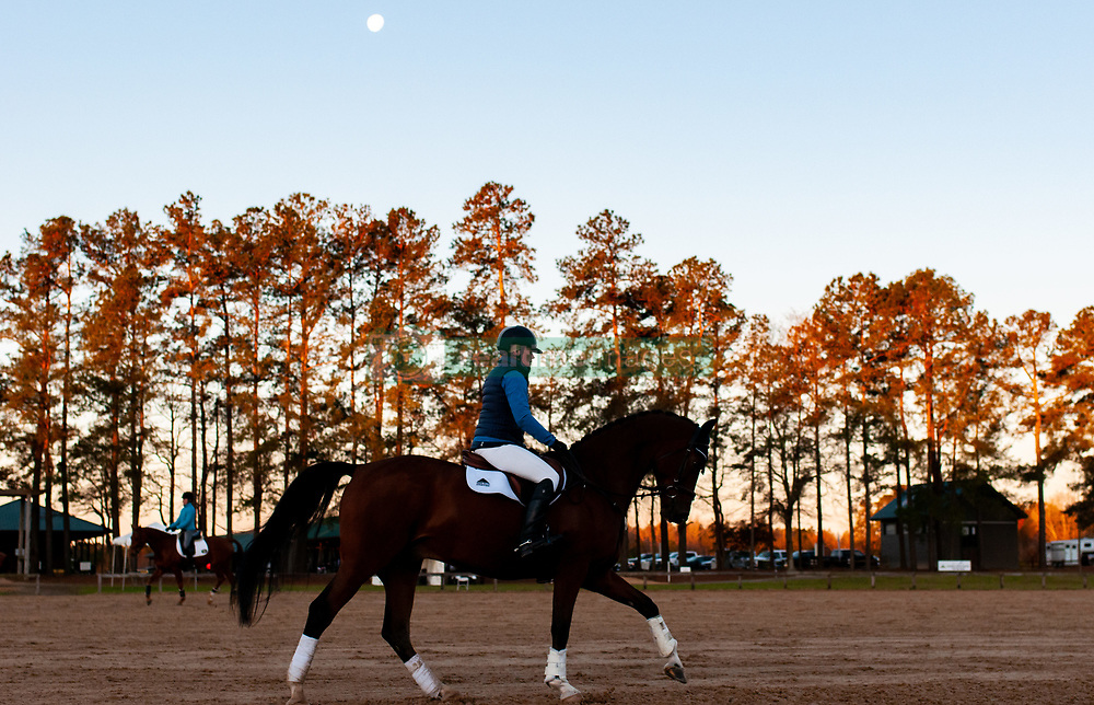 March 22, 2019 - Raeford, North Carolina, US - March 23, 2019 - Raeford, N.C., USA - A rider exercises her horse in the dressage warm-up ring as the moon sets at the sixth annual Cloud 11-Gavilan North LLC Carolina International CCI and Horse Trial, at Carolina Horse Park. The Carolina International CCI and Horse Trial is one of North AmericaÃ•s premier eventing competitions for national and international eventing combinations, hosting International competition at the CCI2*-S through CCI4*-S levels and National levels of Training through Advanced. (Credit Image: © Timothy L. Hale/ZUMA Wire)