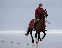 © Licensed to London News Pictures. <br /> 01/01/2017. <br /> Saltburn by the Sea, UK.  <br /> <br /> A man gallops along the beach on New Year's Day at Saltburn beach.<br /> <br /> <br /> <br /> Photo credit: Ian Forsyth/LNP