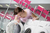 Young woman chooses washing machine in shopping mall Voronezh