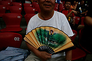"""A Chinese man cools himself with a fan bearing the picture of a young Mao Zedong at the National Stadium, also known as the """"Bird's nest"""" in Beijing , China, Wednesday, Aug.20, 2008. It is one of the strangest things about the Olympics: From far away, it looks very close. Watching the Olympics on television, the athletes are right in front of you.  Up close, though, it's normally a different story. From the spectators' stands, the athletes are often just distant specks amid the enormity of some of the largest sports stadiums in the world.(Elizabeth Dalziel)"""