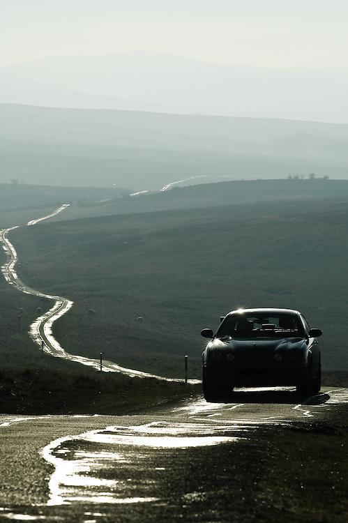 Jaguar car driving along a remote fell road at Great Asby Scar, Cumbria, England, UK