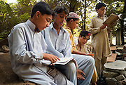 Young boys sit on makeshift brick chairs in the grounds of their destroyed Nazarabad Boys School in SWAT...Rubble from the destroyed school has been used as improvised chairs in the shady areas underneath trees...Some pupils have returned to the makeshift open-air class rooms whilst others still fear the return of the Taliban and choose to stay away from lessons. .