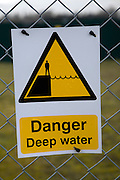 Danger deep water warning sign on chain link fence