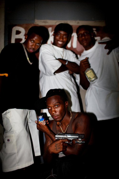 """Winky Williams (front) Demetris """"Butta"""" Anderson (back L), Martez Maggitt (back center) and another friend mug for the camera during another late night of drinking, selling drugs, gambling and talking shit on the corner in the Baptist Town neighborhood of Greenwood, Mississippi on Saturday, July 3, 2010. Since this image was made Winky moved to Texas to start a new life but was arrested and sent back, Butta was shot and killed, and Martez  was sent to prison."""