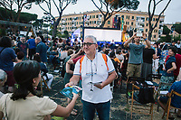 """ROME, ITALY - 27 JUNE 2017: A program of the """"Don Giovanni OperaCamion"""", an open-air opera performed on a truck, is distributed to the audience shortly before the premiere in San Basilio, a suburb in Rome, Italy, on June 27th 2017.<br /> <br /> Director Fabio Cherstich's idae of an """"opera truck"""" was conceived as a way of bringing the musical theatre to a new, mixed, non elitist public, and have it perceived as a moment of cultural sharing, intelligent entertainment and no longer as an inaccessible and costly event. The truck becomes a stage that goes from square to square with its orchestra and its company of singers in Rome. <br /> <br /> """"Don Giovanni Opera Camion"""", after """"Don Giovanni"""" by Wolfgang Amadeus Mozart is a new production by the Teatro dell'Opera di Roma, conceived and directed by Fabio Cherstich. Set, videos and costumes by Gianluigi Toccafondo. The Youth Orchestra of the Teatro dell'Opera di Roma is conducted by Carlo Donadio."""
