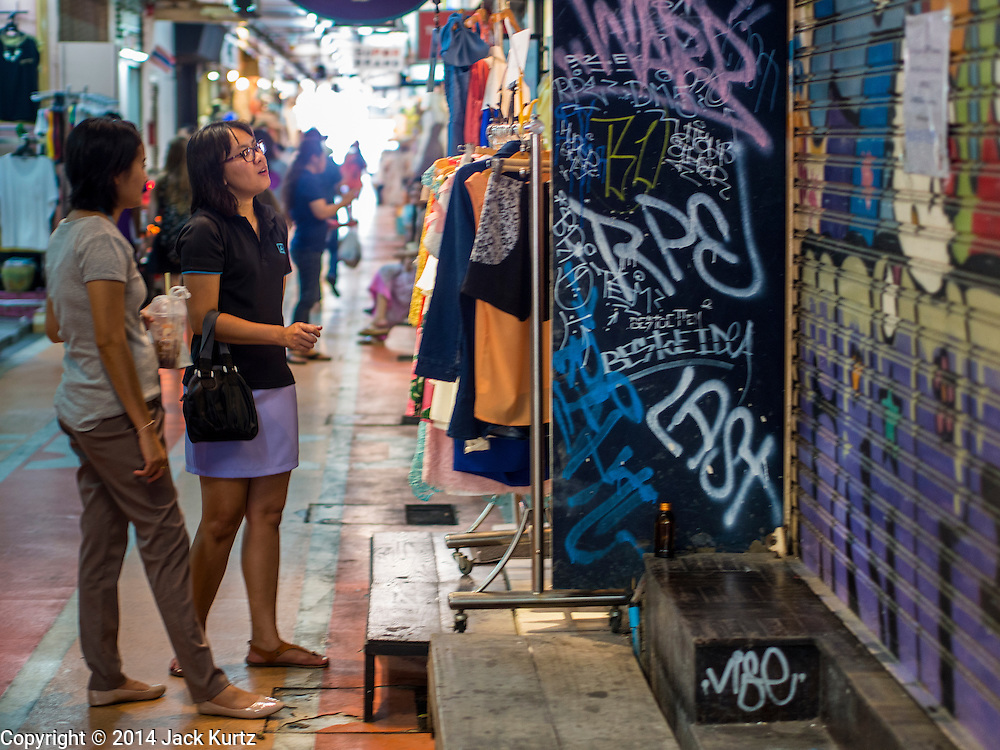 15 JULY 2014 - BANGKOK, THAILAND: Shoppers look at a clothing boutique in Siam Square, a shopping and entertainment area in Bangkok. There is a range of shops and services, including tutor schools, restaurants, cafe, designer clothing boutiques, record stores, bookshops, Hard Rock Cafe and banks in the area. Siam Square is owned by Chulalongkorn University and is managed by its Property Management Office, known as the Chula Property.    PHOTO BY JACK KURTZ