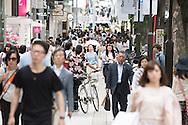 Large crowd of Japanese people walking in busy urban environment in Omotesando shopping district of the capital city of Japan, Tokyo.