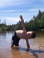 Portrait of a happy smiling child, 3 year old boy, playing in lake water in the nature. Ontario, Canada.
