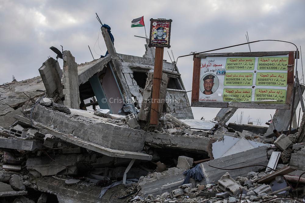 """Shejaya, quartiere a nord della striscia di Gaza. Una delle zone piu colpite dall'attacco israeliano """"Margine protettivo"""". Il quartiere è stato raso al suolo. La popolazione, a distanza di sei mesi dalla fine della guerra, vive tra le macerie della propria casa, al freddo, senza luce, gas e acqua. Nella foto la vista di una casa distrutta e la foto un un martire, un ragazzo delle brigate di Hamas Al Quassam."""