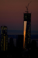Pastel colors streak across the sky in the early morning hours over lower Manhattan.  The colors of the rising sun reflect off the Freedom Tower.