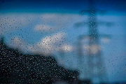 Out of focus power pylon seen through a window covered with raindrops. The focus is on the drops of water on the windscreen