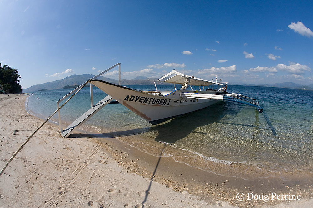 traditional Philippine outrigger fishing banca, in use as dive boat, on beach at Camayan Beach Resort, Subic Bay Freeport Zone, Philippines