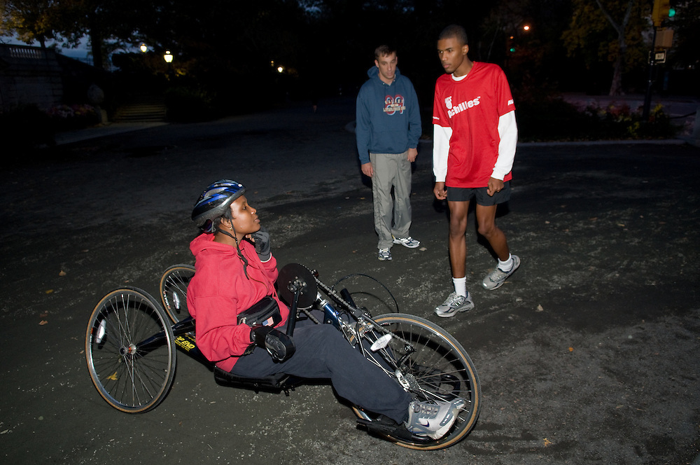 New York, New York, 2008:  Nadine McNeil trains for this sundays ING New York City Marathon on a cool evening night in central park. McNeil is a hand cyclist who will be competing in her fifth marathon this sunday. What makes this marathon different and even more challenging for her versus other marathons that she has partaken in, is that her 18  year old son, Tyler, will be running his first marathon this weekend. Tyler, who was born with autism, will have a guide running with him during the marathon.  Nadine with her son Tyler and his running guide.          Photos by Tiffany L Clark