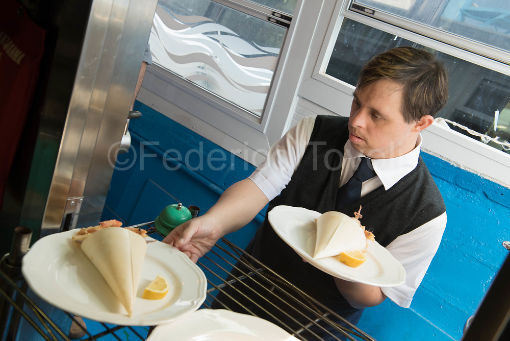 David withdrawing dishes from cuisine, in this case fry served on absorbent paper