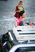"""Apr. 13, 2010 - Bangkok, Thailand: A boy squirts a motorcycle taxi with water during Songkran festivities in central Bangkok. Songkran is the Thai New Year's holiday, celebrated from April 13 - 15. This year's official celebrations have been cancelled because of the Red Shirt protests but Thais are still marking the holiday. It's one of the most popular holidays in Thailand. Songkran originally was celebrated only in the north of Thailand, and was adapted from the Indian Holi festival. Except the Thais throw water instead of colored powder. The throwing of water originated as a way to pay respect to people, by capturing the water after it had been poured over the Buddhas for cleansing and then using this """"blessed"""" water to give good fortune to elders and family by gently pouring it on the shoulder. Among young people the holiday evolved to include dousing strangers with water to relieve the heat, since April is the hottest month in Thailand (temperatures can rise to over 100°F or 40°C on some days). This has further evolved into water fights and splashing water over people riding in vehicles. The water is meant as a symbol of washing all of the bad away and is sometimes filled with fragrant herbs when celebrated in the traditional manner. Photo by Jack Kurtz"""