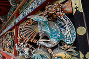 "Ornate wood bird carving at 1600s Toshogu Shrine in Nikko, a UNESCO World Heritage site in Japan. Toshogu Shrine is the final resting place of Tokugawa Ieyasu, the founder of the Tokugawa Shogunate that ruled Japan for over 250 years until 1868. Ieyasu is enshrined at Toshogu as the deity Tosho Daigongen, ""Great Deity of the East Shining Light"". Initially a relatively simple mausoleum, Toshogu was enlarged into the spectacular complex seen today by Ieyasu's grandson Iemitsu during the first half of the 1600s. The lavishly decorated shrine complex consists of more than a dozen buildings set in a beautiful forest. Countless wood carvings and large amounts of gold leaf were used to decorate the buildings in a way not seen elsewhere in Japan. Toshogu contains both Shinto and Buddhist elements, as was common until the Meiji Period when Shinto was deliberately separated from Buddhism. Toshogu is part of Shrines and Temples of Nikko UNESCO World Heritage site."