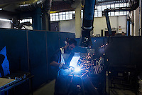 SOVERIA MANNELLI, ITALY - 16 NOVEMBER 2016: A workers welds the steel structure of a chair here in the warehouse of Camillo Sirianni, a school furniture manifacturer in Soveria Mannelli, Italy, on November 16th 2016.<br /> <br /> Camillo Sirianni is a third generation family business that started as a family mechanized carpentry in 1909 and transformed into a leading school furniture manufacturer. In a high-tech warehouse in the outskirts of Soveria Mannelli, they assemble thousands of Calabrian beechwooden, colorful desks, benches, closets and other accessories that are later shipped to many corners of the globe, from the United Kingdom to the Emirates, from central America to Polynesia.<br /> <br /> Soveria Mannelli is a mountain-top village in the southern region of Calabria that counts 3,070 inhabitants. The town was a strategic outpost until the 1970s, when the main artery road from Naples area to Italy's south-western tip, Reggio Calabria went through the town. But once the government started building a motorway miles away, it was cut out from the fastest communications and from the most ambitious plans to develop Italy's South. Instead of despairing, residents benefited of the geographical disadvantage to keep away the mafia infiltrations, and started creating solid businesses thanks to its administrative stability, its forward-thinking mayors and a vibrant entrepreneurship numbering a national, medium-sized publishing house, a leading school furniture manufacturer and an ancient woolen mill.