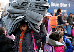 A migrant child carries blankets as refugees and migrants disembark from the passenger ferry Blue Star1 at the port of Piraeus, near Athens, Greece, January 31, 2016. Picture taken January 31, 2016. REUTERS/Darrin Zammit Lupi MALTA OUT. NO COMMERCIAL OR EDITORIAL SALES IN MALTA      TPX IMAGES OF THE DAY      - RTX24VE4