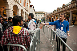 © Licensed to London News Pictures. 21/09/2012. LONDON, UK. A member of Apple Staff hands out bottles of water to people queuing to purchase iPhone 5 handsets in London today (21/09/12). The iPhone 5, Apples latest mobile phone, went on sale in the UK today, with customers restricted to just two phones per-person and many buying in cash. Photo credit: Matt Cetti-Roberts/LNP