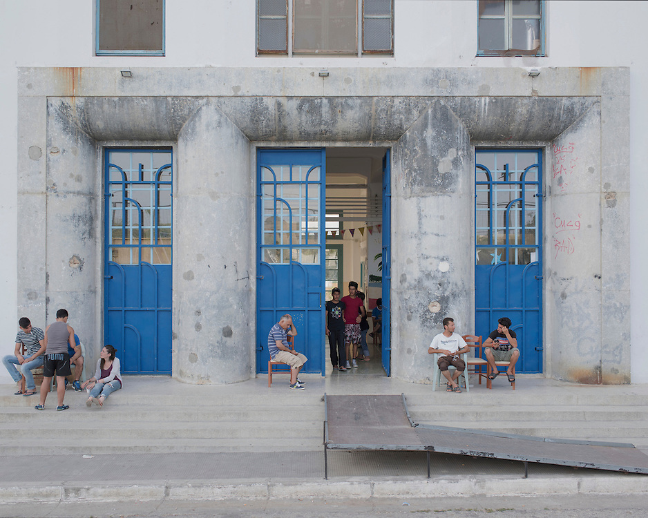 Refugees outside the main entrance of the PIKPA building. The refuge was opened in January 2016 by the Leros Solidarity Network as a shelter for families and unaccompanied minors. The building has about 20 rooms accommodating 102 people.