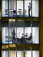 Business man text messaging on floor above group of business people at office meeting view from building exterior