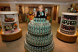© licensed to London News Pictures. London, UK 23/04/2012. A Fortnum & Mason staff posing on top of a Heinz can pile as Heinz, beans brand, launching a limited edition set of cans to honour the Queens Diamond Jubilee at Fortnum & Mason, this morning (23/04/12). Photo credit: Tolga Akmen/LNP